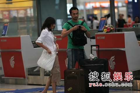 装扮休闲的两人一人一个行李箱并肩同行
